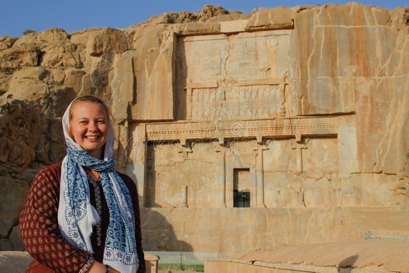 El turista de la mujer joven con una cabeza cubierta se coloca en el fondo de los bajorrelieves famosos de la capital de Persia I foto de archivo libre de regalías