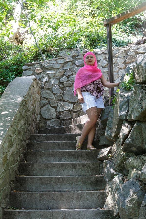 El turista de la mujer joven sube los pasos antiguos de la piedra ascendentes foto de archivo libre de regalías