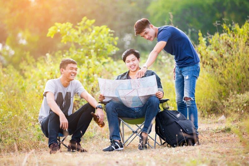 El turista de tres jóvenes discute el viaje fotos de archivo libres de regalías