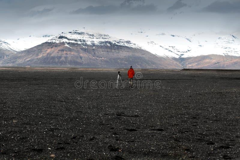 El turista del fotógrafo se coloca en las montañas y de un trípode t foto de archivo libre de regalías