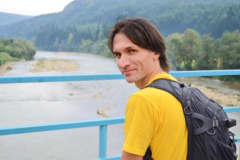 El turista del hombre en una camiseta amarilla con una mochila se coloca en un puente sobre un río de la montaña en el fondo de l imagenes de archivo