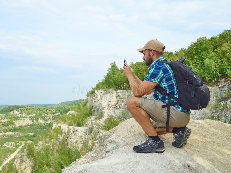El turista del hombre está utilizando un smartphone mientras que se sienta en el borde del cli foto de archivo