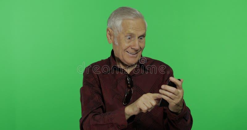 El turista del hombre mayor trabaja en un smartphone en el fondo dominante de la croma foto de archivo