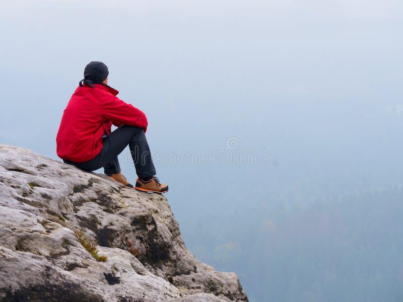 El turista del hombre se sienta en cumbre expuesta de la roca Punto de visión sobre el hombre triste de la niebla que vigila el v fotos de archivo libres de regalías