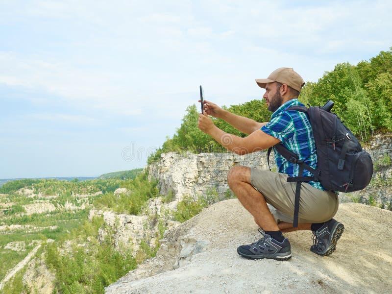 El turista del hombre utiliza la tableta que se sienta en el borde del acantilado en el mou fotos de archivo libres de regalías
