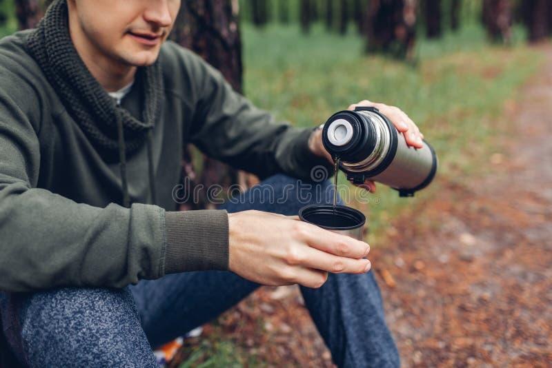 El turista del hombre vierte t? caliente fuera del termo en bosque de la primavera que acampa, concepto el viajar y del deporte foto de archivo libre de regalías