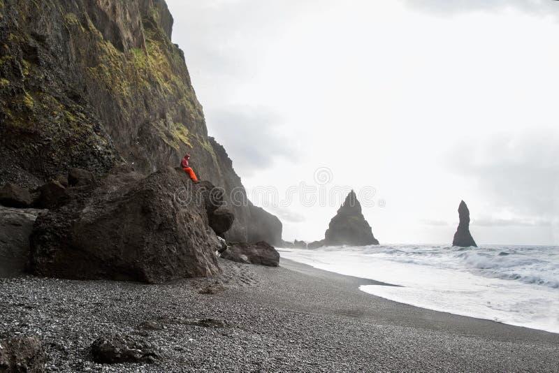 El turista del individuo se sienta encima de una montaña en Islandia, el concepto de imágenes de archivo libres de regalías