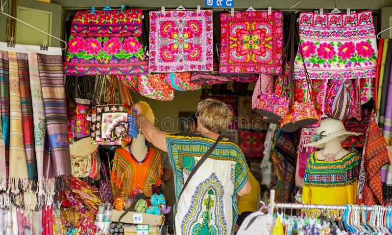 El turista es recuerdo y ropa locales que hacen compras foto de archivo