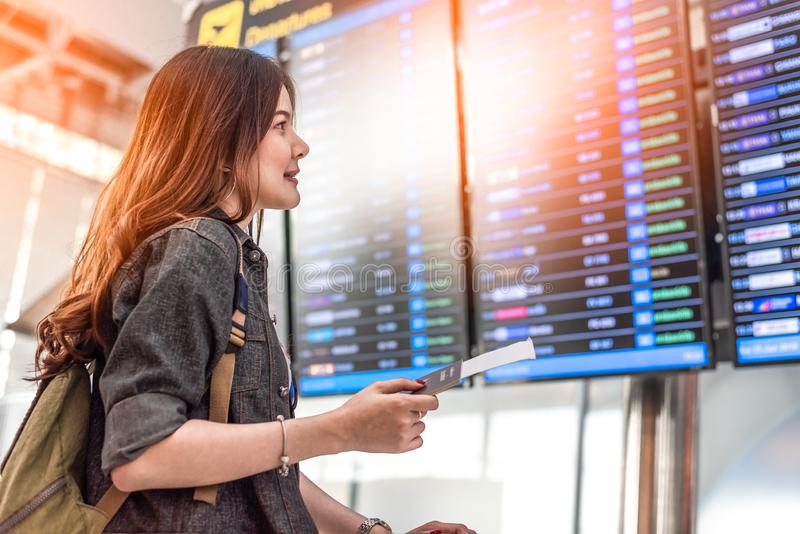 El turista femenino asiático de la belleza que mira los horario de vuelo para comprobar saca tiempo Gente y concepto de las forma imagen de archivo