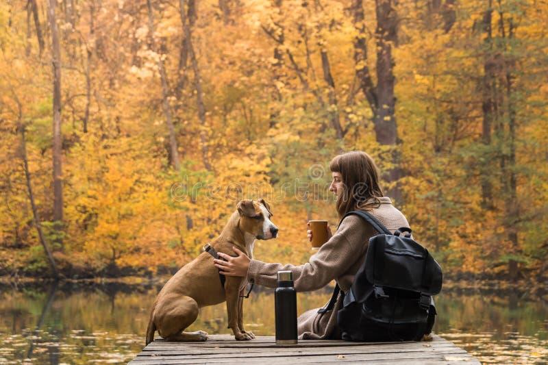 El turista femenino se sienta con el perro cerca del lago y goza de la taza de consumición hermosa de la opinión del otoño de caf fotos de archivo libres de regalías