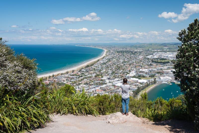 El turista fotografía la ciudad de Tauranga desde arriba del soporte Maunganui fotografía de archivo libre de regalías