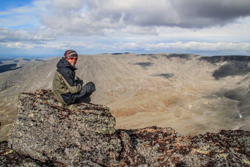 El turista masculino blanco caucásico en ropa de deportes, piel de ante y vidrios se sienta en una roca imágenes de archivo libres de regalías