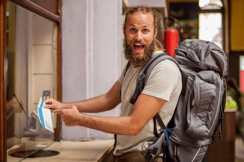 El turista masculino del backpacker feliz y eufórico muestra el boleto para el suyo fotos de archivo libres de regalías