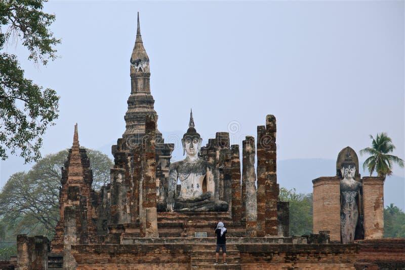 El turista masculino en pañuelo del este está mirando en el parque histórico famoso de Sukhothai de la estatua grande del budda fotos de archivo libres de regalías