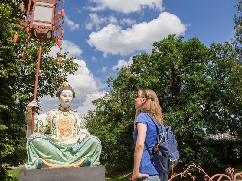 El turista mira las estatuas chinas antiguas en el puente chino grande en Tsarskoye Selo Rusia fotos de archivo