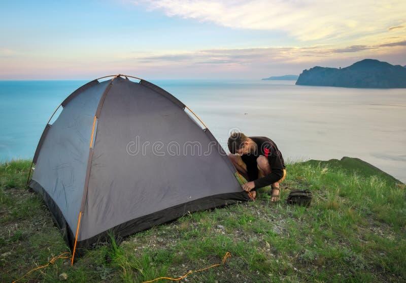 El turista puso una tienda en el top de una montaña fotografía de archivo