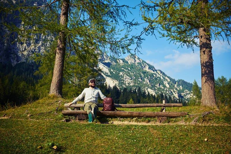 El turista se está sentando en el banco después de subir la montaña fotos de archivo libres de regalías
