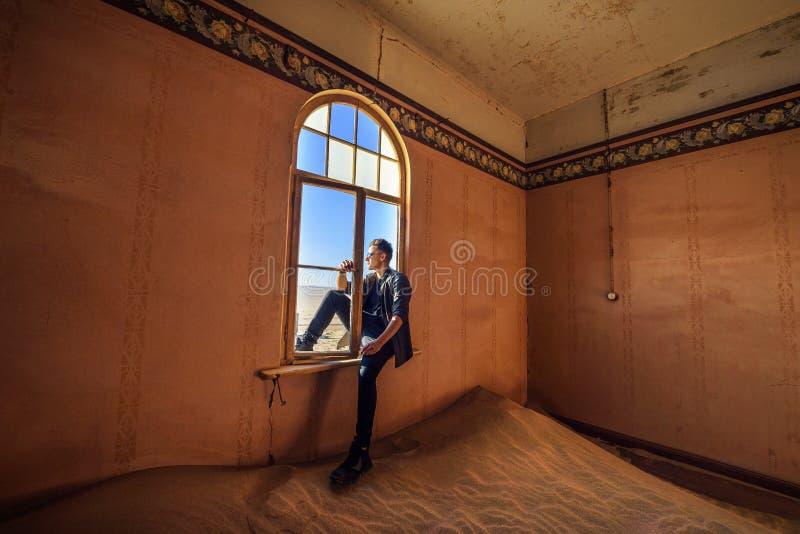 El turista se sienta en la ventana de un cuarto en el pueblo fantasma Kolmanskop, Namibia imagen de archivo libre de regalías