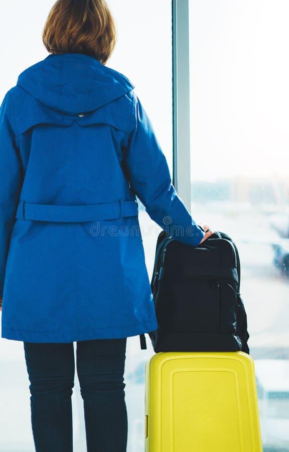 El turista trasero del viajero de la visión con la mochila amarilla de la maleta se está colocando en el aeropuerto en ventana gr foto de archivo libre de regalías
