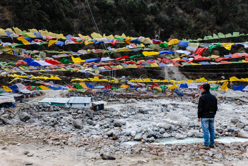 El turista ve banderas tibetanas del rezo el agitar y swaddled con los árboles una montaña en sideway sobre el río congelado en T foto de archivo libre de regalías