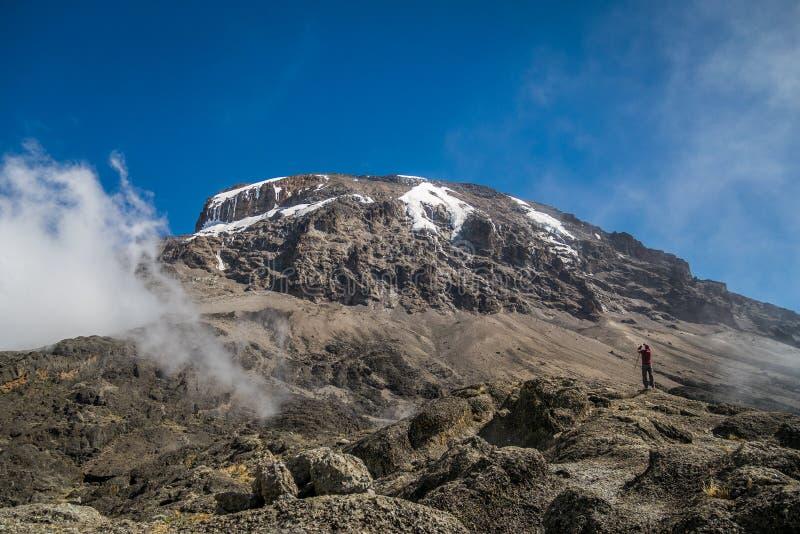 El turista y Kibo enarbolan en el monte Kilimanjaro, Tanzania fotografía de archivo libre de regalías