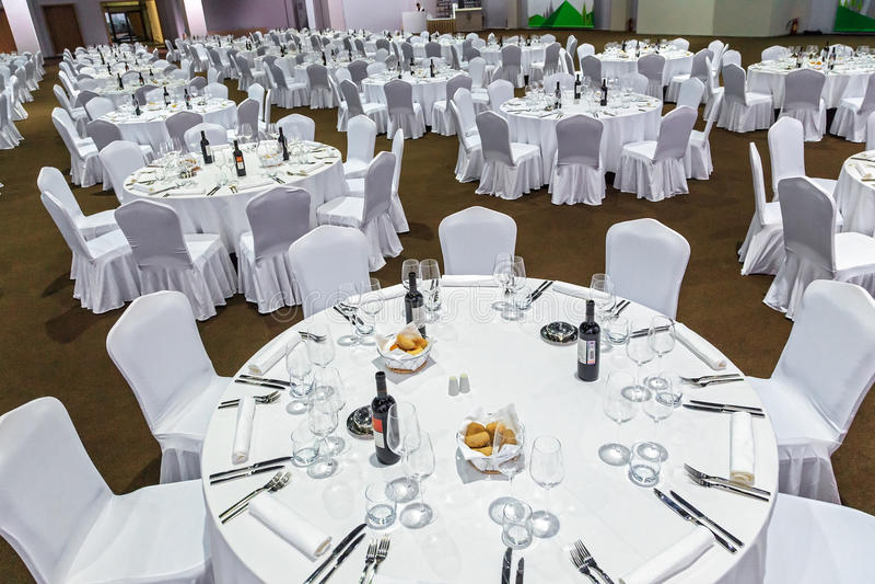El un montón de mesas redondas grandes y las sillas cubiertas con el mantel blanco se fijan para una comida en el restaurante de  imágenes de archivo libres de regalías