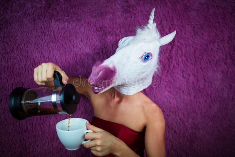 El unicornio divertido de la muchacha vierte té Mujer joven extraña en máscara cómica foto de archivo