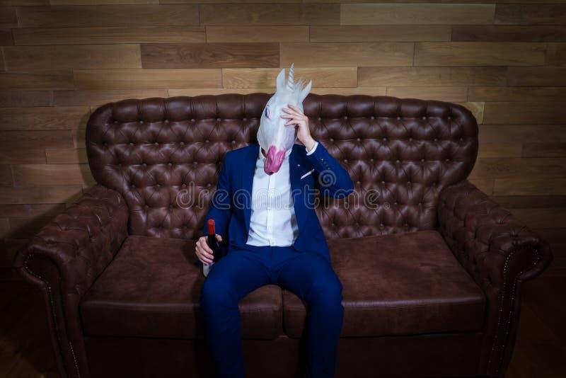 El unicornio divertido en traje elegante se sienta en el sofá con la botella de vino fotos de archivo libres de regalías