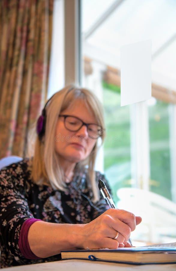 El uno mismo emplyed la observación de la mujer webinar en su ordenador portátil, llevando los auriculares fotografía de archivo