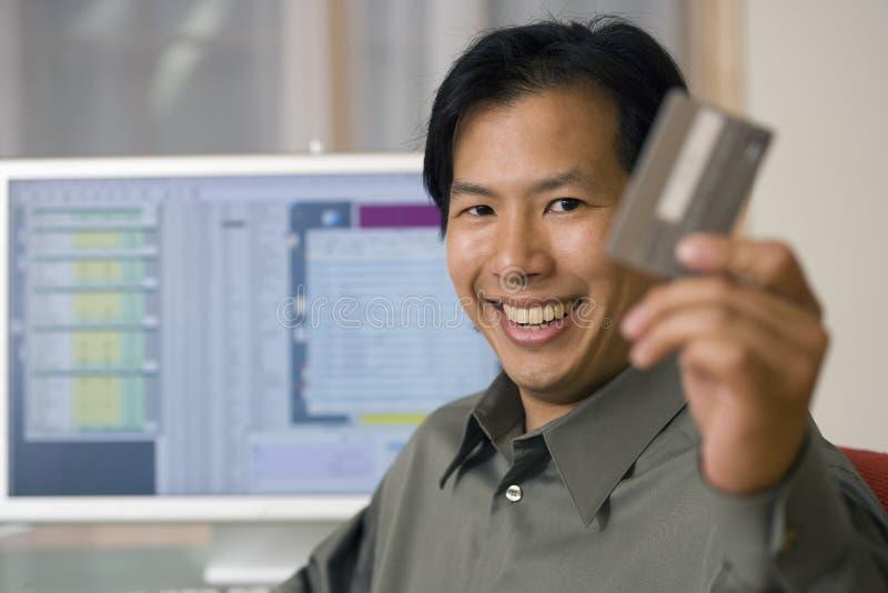 El usar asiático del hombre de la tarjeta de crédito y ordenador fotografía de archivo libre de regalías