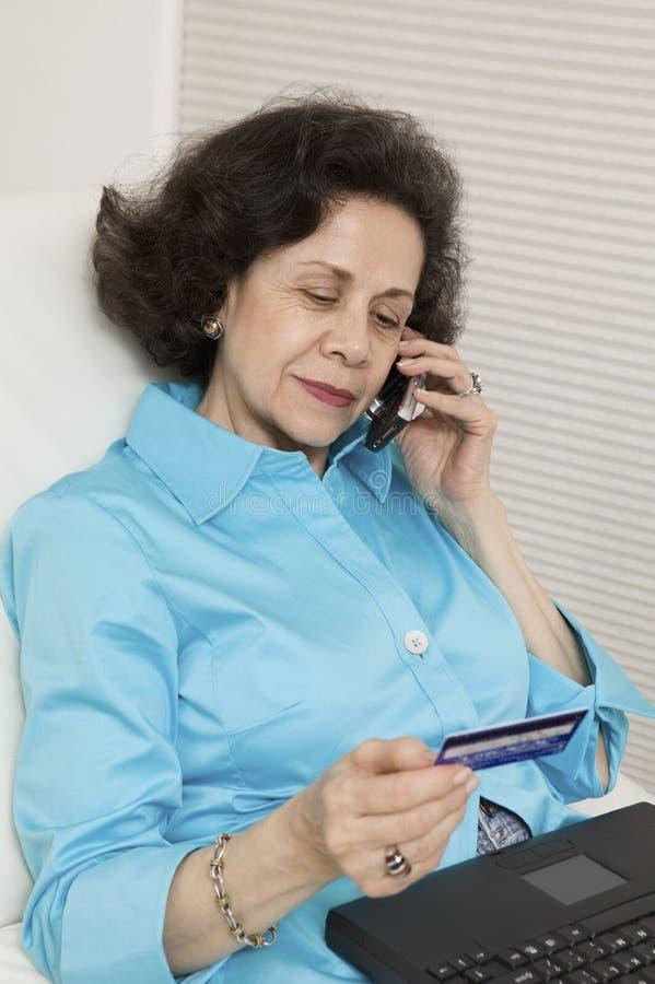 El usar de la mujer de la tarjeta de crédito y teléfono foto de archivo