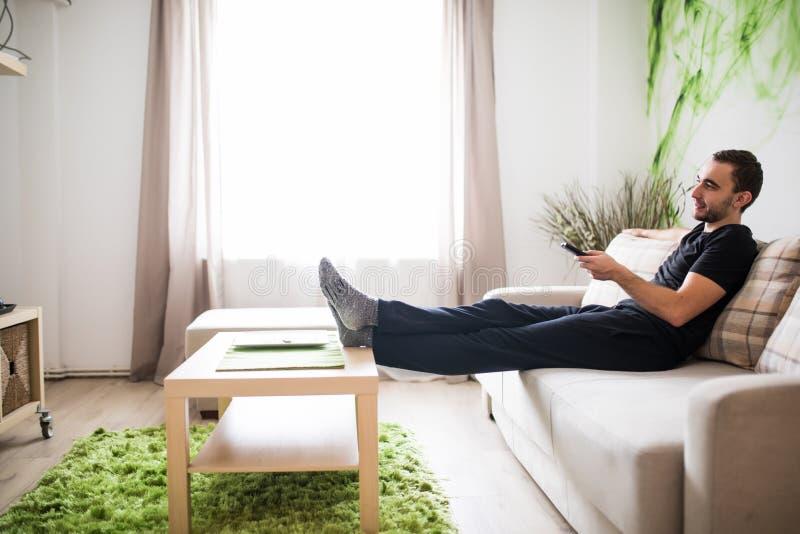 El usar del hombre joven teledirigido mientras que se sienta en el sofá en sala de estar imagenes de archivo