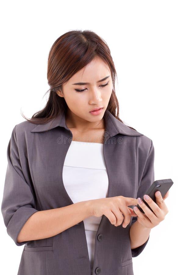 El usar trastornado de la mujer de negocios, mandando un SMS con smartphone foto de archivo libre de regalías