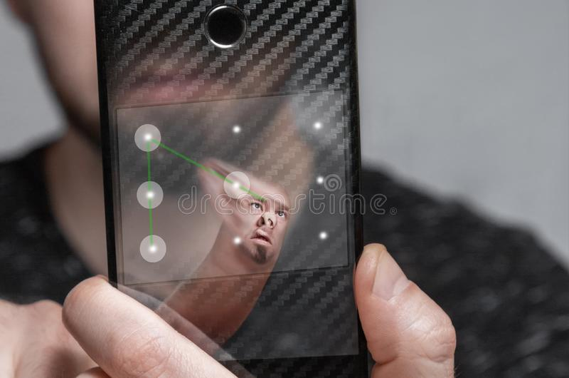 El usuario de Smartphone pasa el sistema de protección biométrico bajo la forma de llave gráfica El concepto de protección de dat imagen de archivo