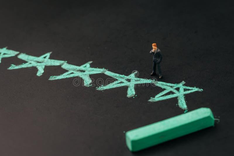 El usuario revisa el grado con las estrellas, concepto de la experiencia del usuario de UX, hombre de negocios miniatura que pien imagen de archivo libre de regalías