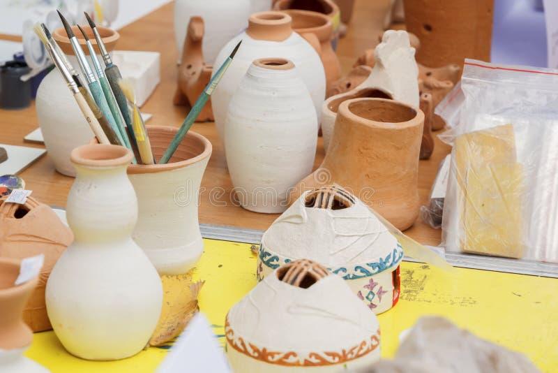 El vajilla y los cepillos de cerámica se colocan en una tabla para pintar imagenes de archivo