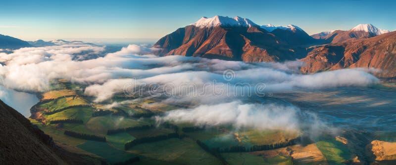 El valle se inunda en niebla en un ambiente de la montaña Sobre se empaña, sólo los altos picos de las montañas foto de archivo