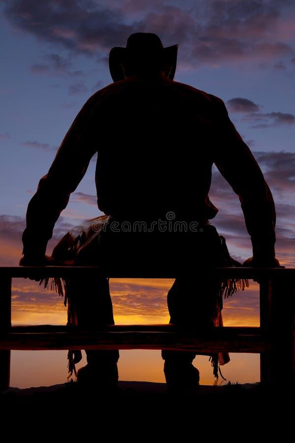 El vaquero de la silueta sienta la cerca fotografía de archivo libre de regalías