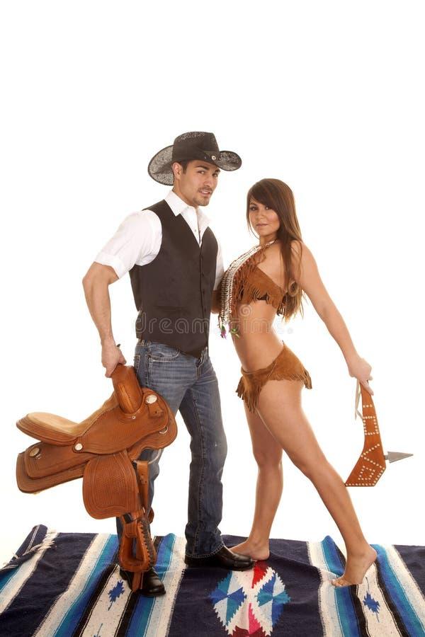 El vaquero y la mujer india ensillan ambos mirada foto de archivo