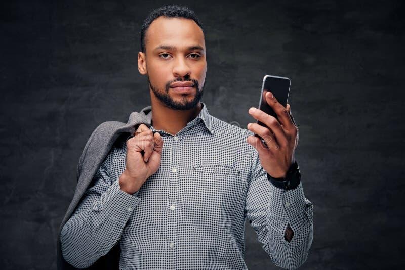 El varón americano negro ocasional vestido sostiene el teléfono elegante fotos de archivo