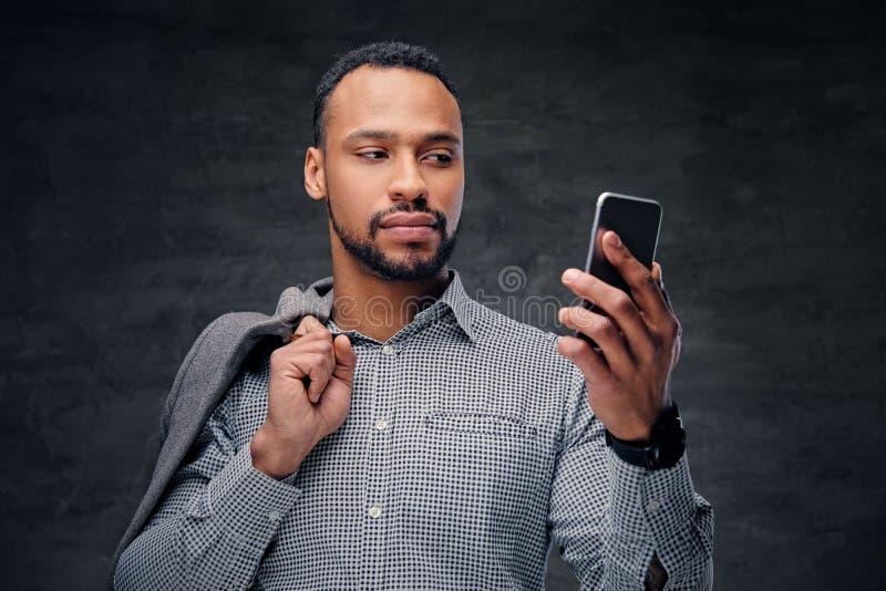 El varón americano negro ocasional vestido sostiene el teléfono elegante foto de archivo