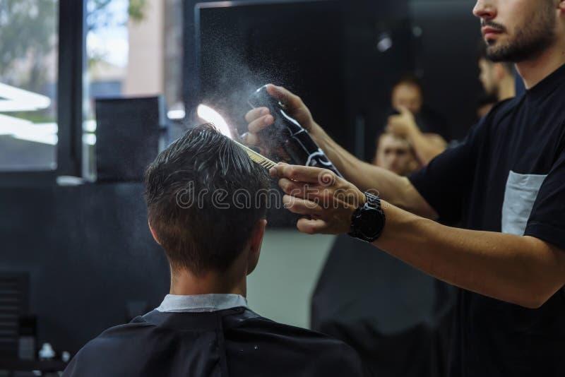 El varón atractivo está consiguiendo un corte de pelo moderno en peluquería de caballeros El peluquero moja el pelo por el espray imagenes de archivo