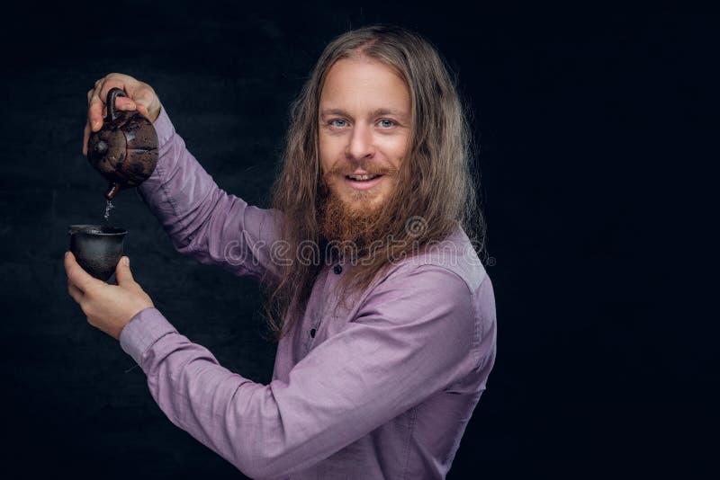 El varón barbudo con el pelo largo vierte té foto de archivo