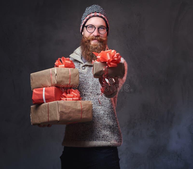El varón barbudo sostiene los regalos de la Navidad foto de archivo