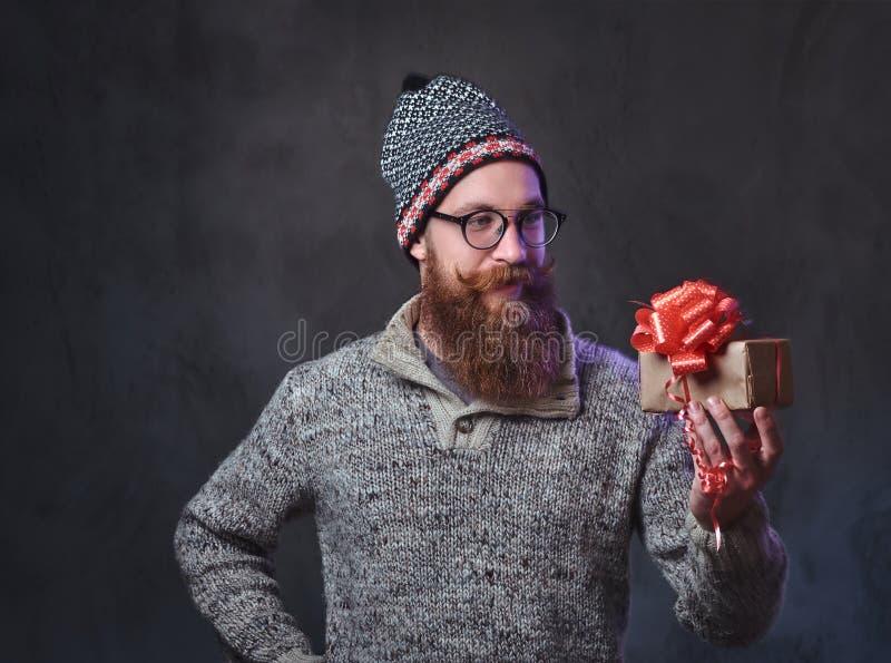 El varón barbudo sostiene los regalos de la Navidad foto de archivo libre de regalías