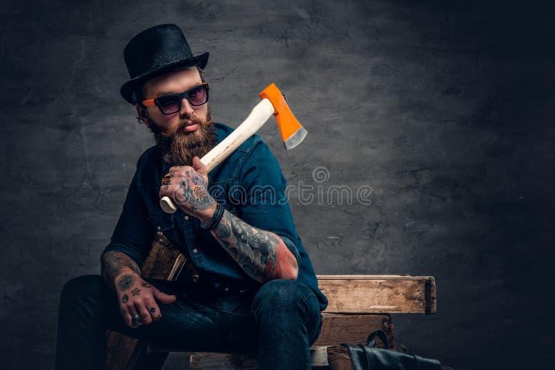 El varón barbudo tatuado sostiene un hacha fotos de archivo
