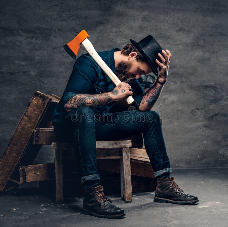 El varón barbudo tatuado sostiene un hacha imagen de archivo