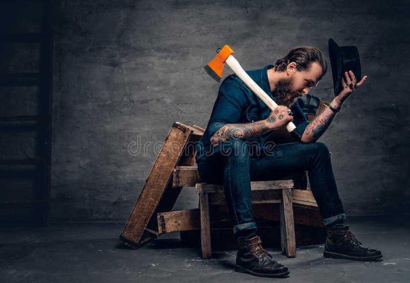 El varón barbudo tatuado sostiene un hacha fotografía de archivo