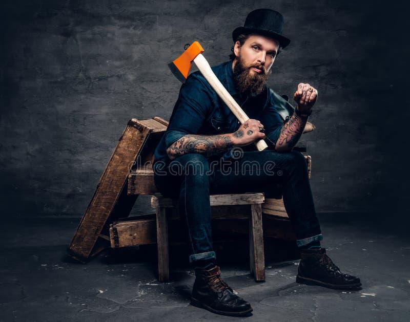 El varón barbudo tatuado sostiene un hacha fotografía de archivo libre de regalías