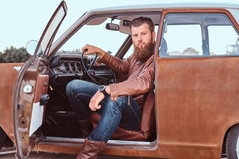 El varón barbudo vestido en chaqueta de cuero marrón se sienta detrás de la rueda de un coche retro adaptado con la puerta abiert fotos de archivo